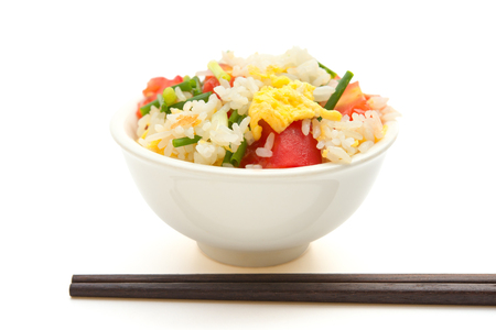 chop sticks: chinese cuisine - homemade fried rice with tomatoes and egg with chop sticks on white
