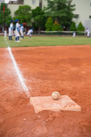 baseball field: baseball and base on baseball field with players on background