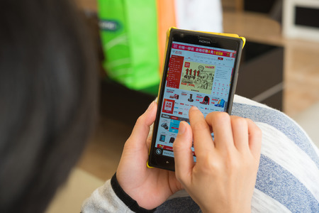Zhongshan,China-November 11, 2015:young woman shopping through mobile on jd on Chinese online shopping day on November 11. Nov 11 is the shopping day in China and many online shops sale things in half price starts from Nov 1 until Nov 11.