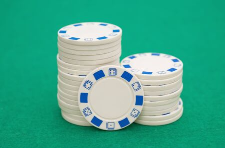 casino table: lots of white poker chips on green casino table