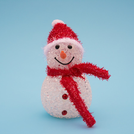 red scarf: smiling toy christmas snowman with red scarf on blue