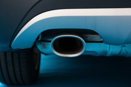 exhaust pipe: exhaust pipe of a black car on blue carpet