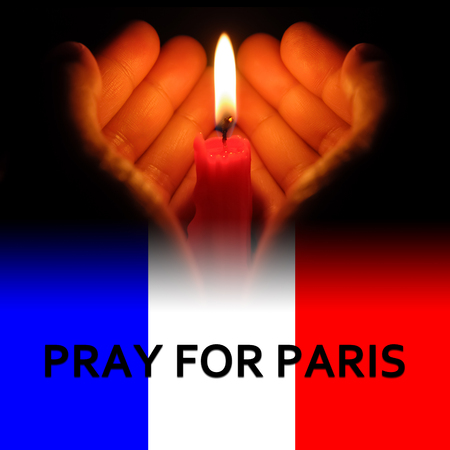 rampage: hands holding a burning candle in dark like a heart with pray for Paris on bottom