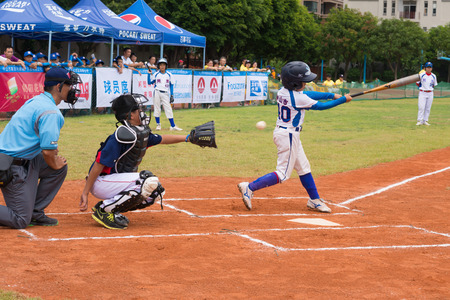 baseman: ZHONGSHAN PANDA CUP, ZHONGSHAN, GUANGDONG - July 23:batter of team Zhongshan TongMao Primary School missed the ball during a match of 2015 National Baseball Championship Group A of Panda Cup against WenZhou XinTianYuan Primary School on July 23, 2015.