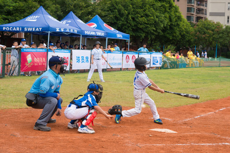 baseman: ZHONGSHAN PANDA CUP, ZHONGSHAN, GUANGDONG - July 23:batter of team BeiJing TianTan DongLi Primary School missed the ball during a match of 2015 National Baseball Championship Group A of Panda Cup against BeiJing TuanJieHu Primary School on July 23, 2015.