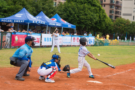 baseman: ZHONGSHAN PANDA CUP, ZHONGSHAN, GUANGDONG - July 23:batter of team BeiJing TianTan DongLi Primary School just missed the ball during a match of 2015 National Baseball Championship Group A of Panda Cup against BeiJing TuanJieHu Primary School on July 23, 2