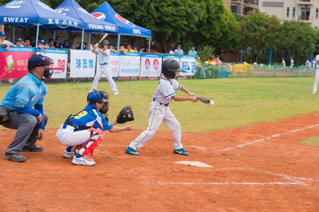 baseman: ZHONGSHAN PANDA CUP, ZHONGSHAN, GUANGDONG - July 23:batter of team BeiJing TianTan DongLi Primary School hit the ball during a match of 2015 National Baseball Championship Group A of Panda Cup against BeiJing TuanJieHu Primary School on July 23, 2015.