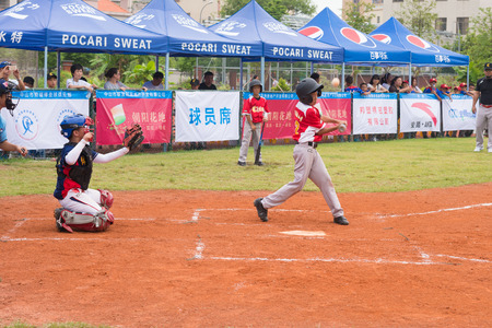 baseman: ZHONGSHAN PANDA CUP, ZHONGSHAN, GUANGDONG - July 23:batter of team WuXi Experimental Primary School hit the bal l and the ball bounced up during a match of 2015 National Baseball Championship Group A of Panda Cup against Sports East Road Primary School on