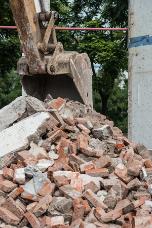 demolishing: excavator demolishing concrete and brick rubble debris vertical