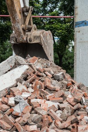 construction machines: excavator demolishing concrete and brick rubble debris vertical