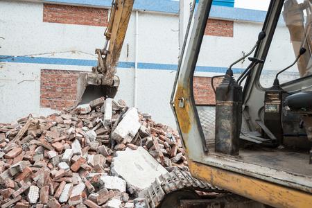 demolishing: excavator demolishing concrete and brick rubble debris horizontal