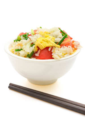 chop sticks: homemade fried rice with tomatoes and egg with chop sticks on white
