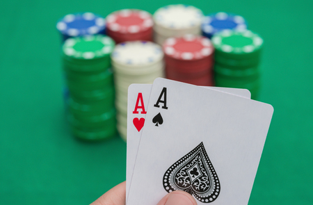 pokers: two Ace of pokers in front of chips on casino table Stock Photo