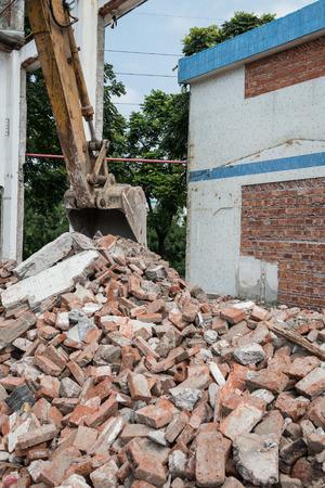 demolishing: excavator demolishing concrete and brick rubble debris vertical