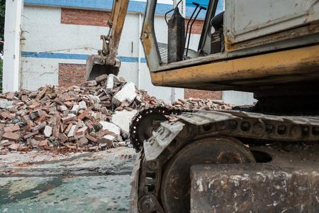 demolishing: excavator demolishing concrete and brick Stock Photo