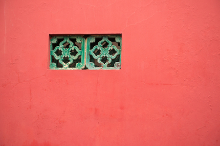 regular people: traditional Chinese window on red wall Stock Photo