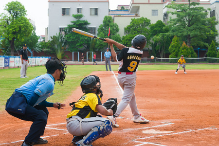 baseman: ZHONGSHAN PANDA CUP, ZHONGSHAN, GUANGDONG - August 3:unknown batter hitting the ball during a match of 2015 National Baseball Championship of Panda Cup on August 3, 2015.