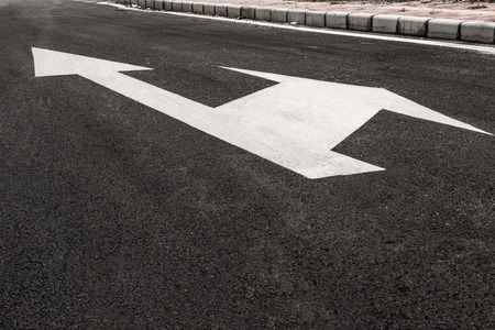 blacktop: white directional arrows on blacktop Stock Photo