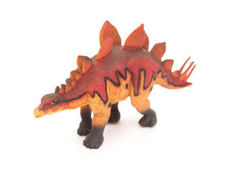 stegosaurus: side view red stegosaurus toy on a white background