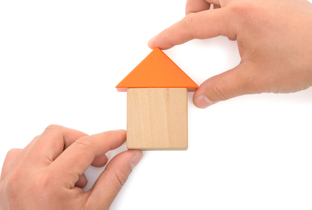 making up: hands making up a house on white Stock Photo