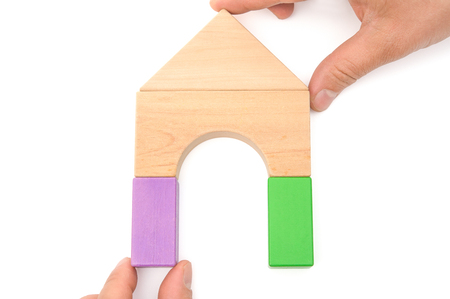 green and purple: hands making up a house on white Stock Photo