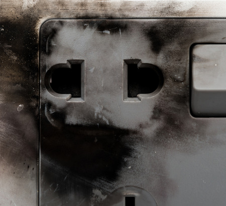 overuse: burnt out electric socket close up