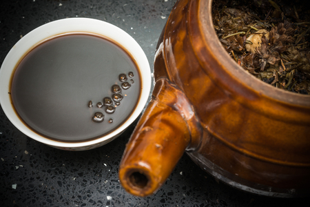bowl of Chinese herbal tea and an enamel pot with herbs nearby