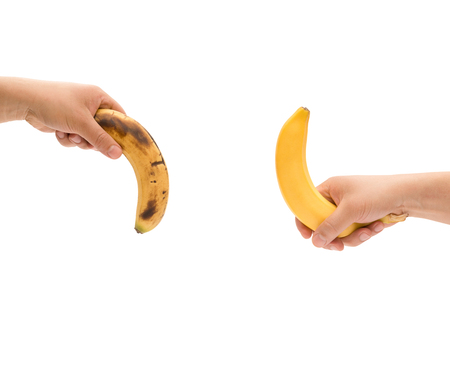 impotent: hands holding a fresh banana up and a over-ripe one down Stock Photo