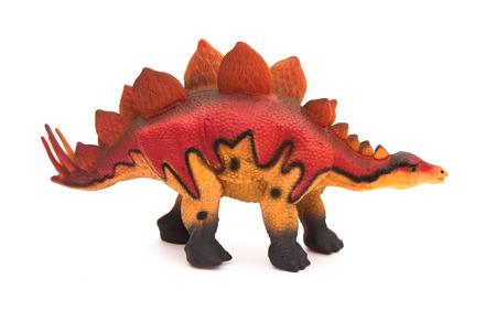 stegosaurus: vista lateral juguete estegosaurio rojo sobre un fondo blanco Foto de archivo