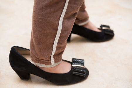 mums: kid wearing mums trendy shoes for fun at home Stock Photo