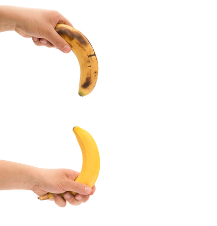 impotent: left hands holding a fresh banana Stock Photo
