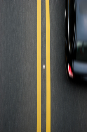 vertical dividers: double yellow lines divider on blacktop with a car passing