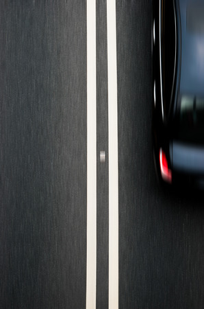 blacktop: double white lines divider on blacktop with a car passing