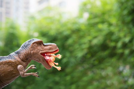 gigantic: gigantic tyrannosaurus catches a smaller dinosaur in front of trees and building Stock Photo