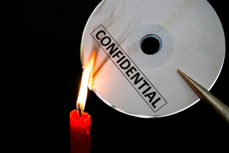 confide: burning a confidential compact disc with candle in dark