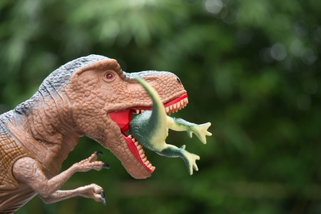 gigantic: gigantic tyrannosaurus catches a smaller dinosaur in front of trees Stock Photo