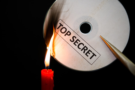 confide: burning a top secret compact disc with candle in dark Stock Photo