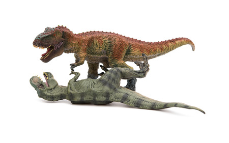 lays down: two tyrannosaurus toys on a white background, one stands and the other lays down
