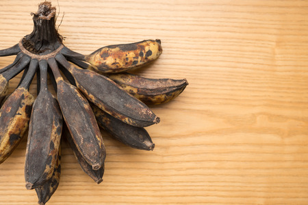 overripe: bunch of black overripe bananas on a wooden background with copy space