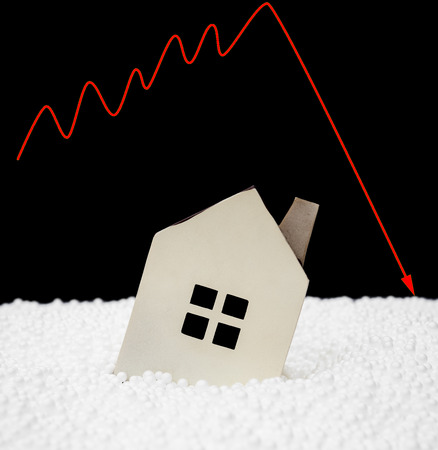 downward: house sinking into polystyrene particle with a downward arrow on background financial concept