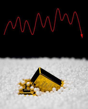 fluctuation: gold bars sink into polystyrene particle and a fluctuation on background monetary concept Stock Photo