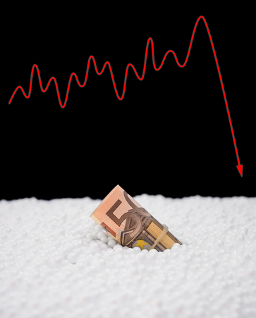 fluctuation: EU money currency sink into polystyrene particle and a fluctuation graphic on background monetary concept