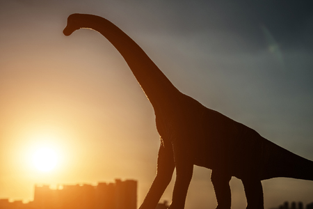 silhouette of brachiosaurus and buildings in sunset time