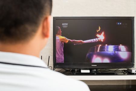 olympic ring: ZHONGSHAN CHINA-August 11:a Chinese watching network TV replaying the torch ignition at the opening ceremony of the 2016 Summer Olympic Games in Rio de Janeiro, Brazil,the 2016 Olympic Games starts on August 5 till to August 21.