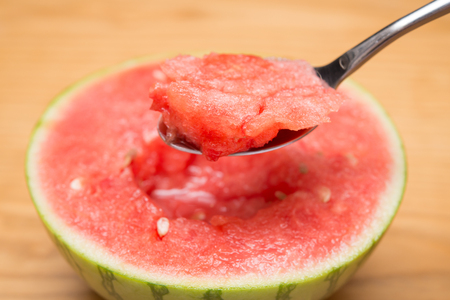 mouthful: spoon taking out mouthful watermelon Stock Photo