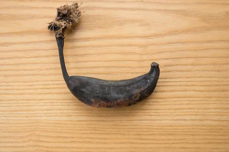 bad banana: black overripe banana on a wooden table