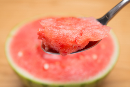 mouthful: spoon taking out mouthful watermelon selective focus Stock Photo