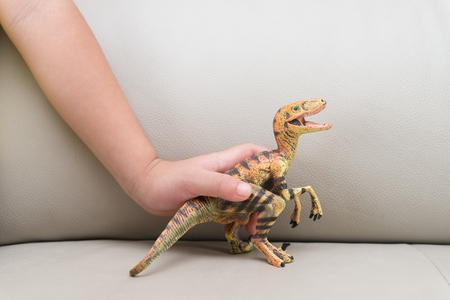 hunter playful: kids hand catching a velociraptor toy on a sofa at home