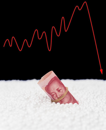 fluctuation: RMB paper currency sink into polystyrene particle and a fluctuation graphic on background monetary concept