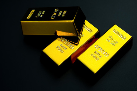 three pieces of gold bar on a black background